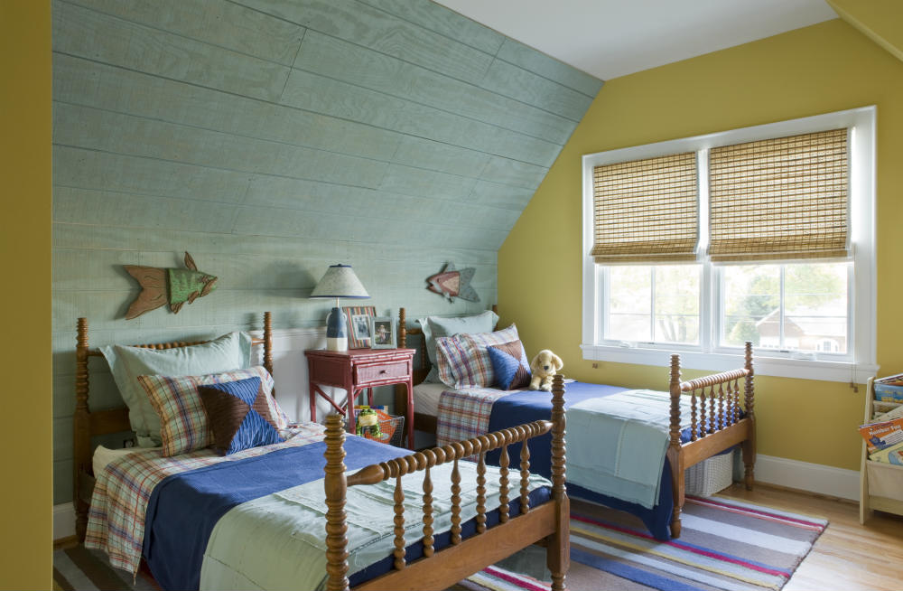 A boy's interest in fishing and camping is captured in a rustic wall of rough-hewn exterior siding, camp-style stripes and plaids, woven wood blinds and hand-carved fish, all styled around the homeowner's childhood beds. </br>(Arlington, Virginia)