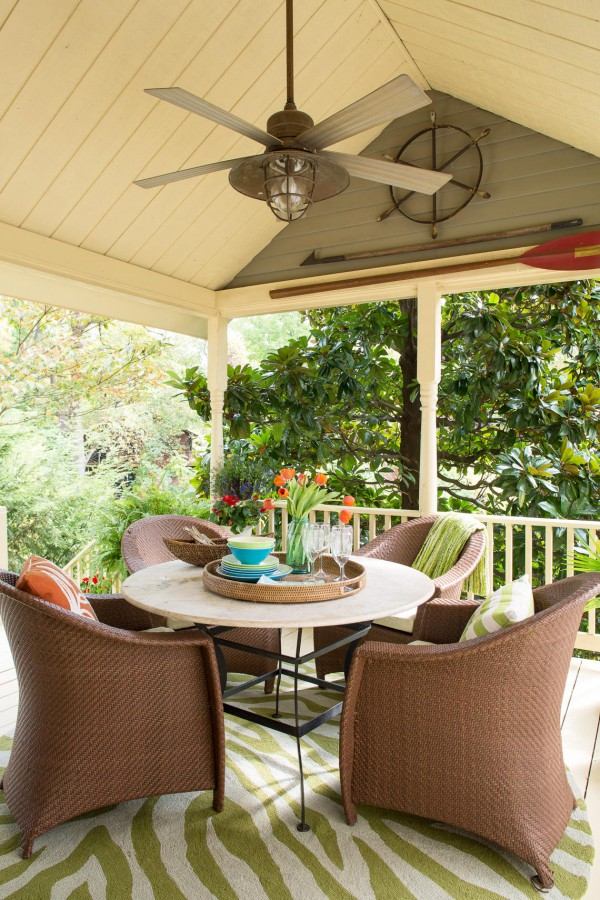 Antique accents grace the inviting covered porch of a Virginia river retreat. <br/>(Montross, Virginia)
