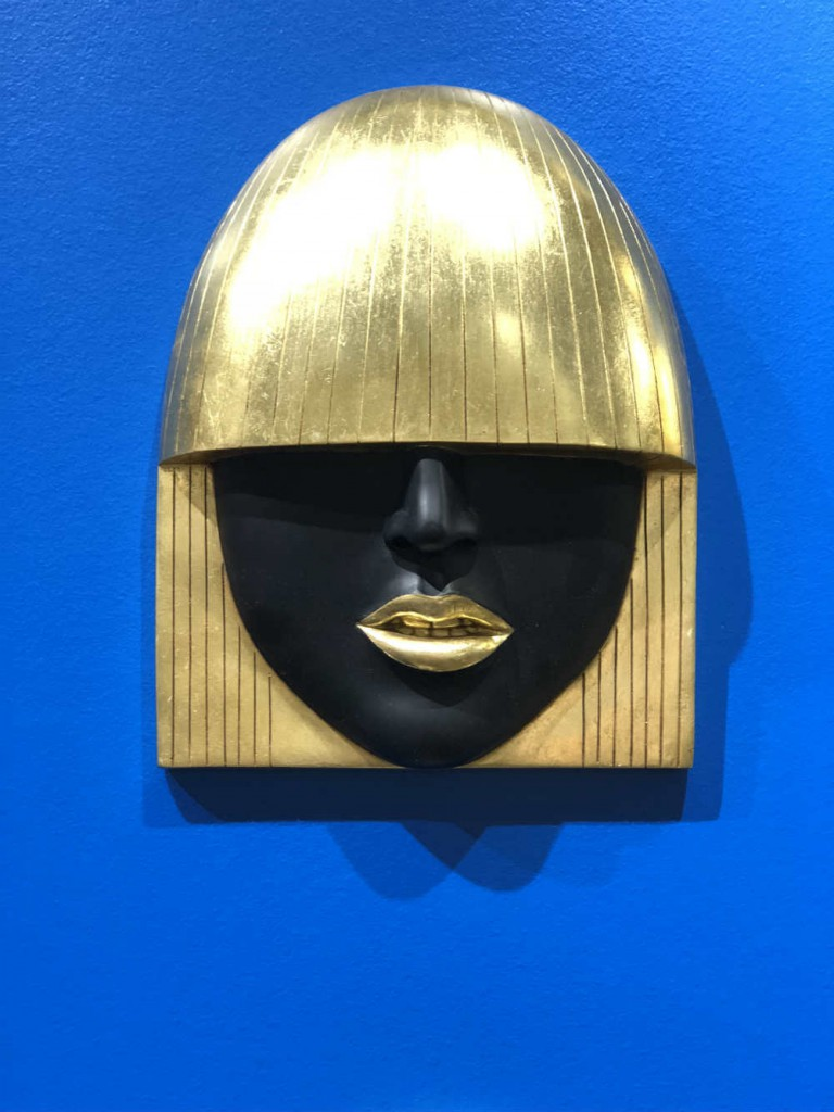 Masks are always cool but the gold and black glamour of this one is particularly stunning on a bright blue wall.